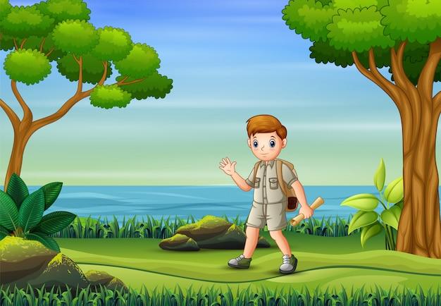 Ein pfadfinderjunge, der mit karten auf der natur wandert