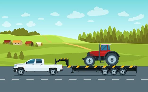 Ein pickup mit anhänger transportiert einen traktor auf der straße