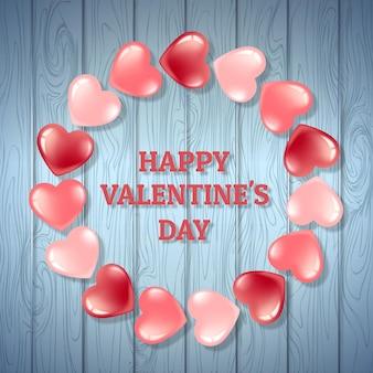 Ein runder rahmen der rosa herzen auf einem hintergrund mit einer blauen holzstruktur. valentinstag