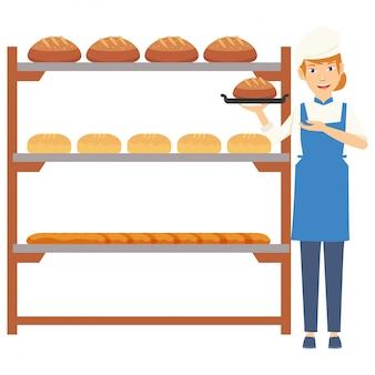 Ein schöner bäcker, der das brot auf platte in der küche hält