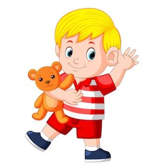 Ein süßer junge spielt mit dem orangefarbenen teddybären