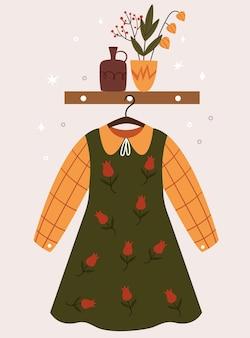 Ein süßes herbstkleid im koreanischen stil, das an einem kleiderbügel hängt. komposition mit vasen. flur zimmer.