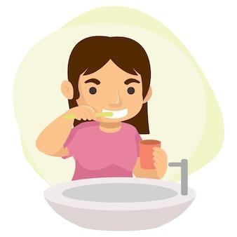 Ein süßes junges mädchen putzt sich nach jeder mahlzeit im badezimmer die zähne