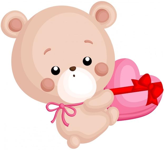 Ein vektor des netten kleinen bären, der einen schokoladen-herz-kasten hält