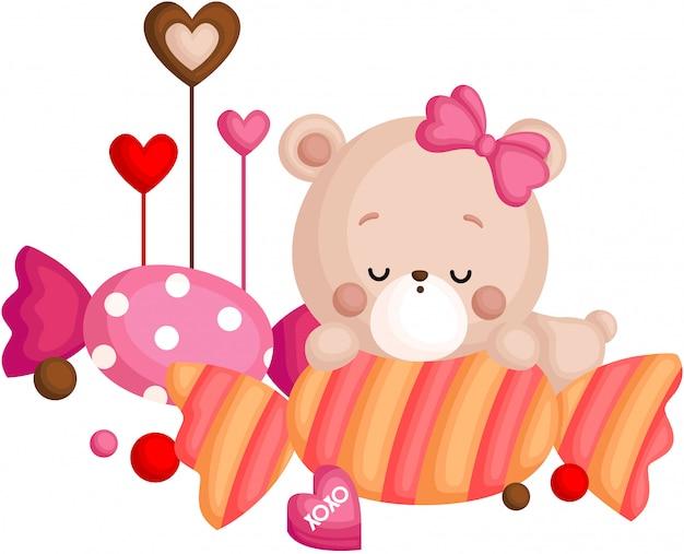 Ein vektor des netten kleinen bären, der über süßigkeit schläft