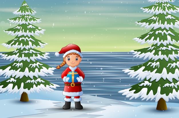 Ein weihnachtsmann, der ein kastengeschenk an der winterlandschaft anhält
