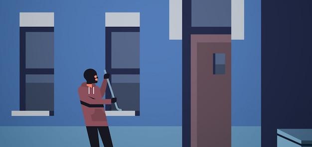 Einbrecher in schwarzer maske mit brechstange