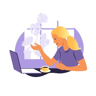 Eine frau arbeitet und kommuniziert auf einem laptop und sitzt zu hause an einem tisch mit einer tasse kaffee und papieren.