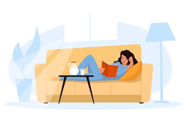 Eine frau, die ein buch zu hause sich entspannt auf dem sofa hält