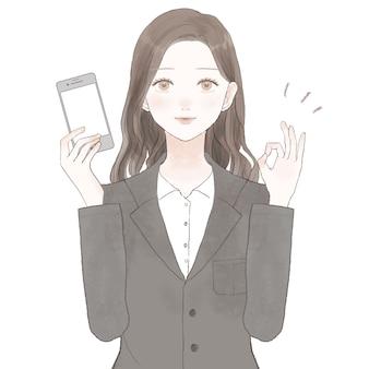 Eine frau in einem anzug, die ein smartphone hält und ein ok-zeichen hält. auf weißem hintergrund.