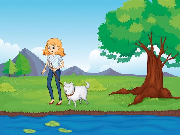Eine frau mit einem hund am fluss entlang spazieren