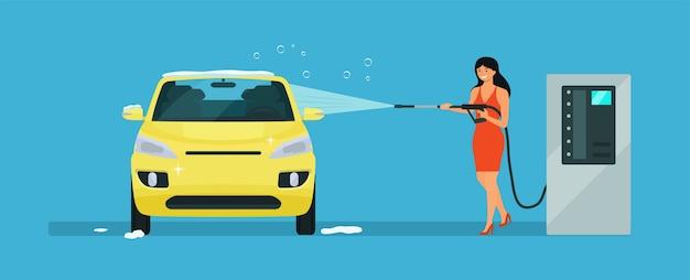 Eine frau wäscht ein auto in einer autowaschanlage