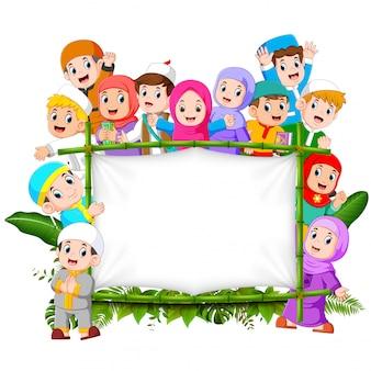 Eine große, glückliche familie hält den holzrahmen des dschungels