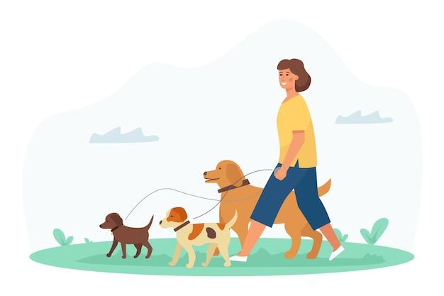 Eine hundewandererin, eine junge hübsche frau, genießt die aktivität im park mit ihren haustieren. tierpflegedienst.