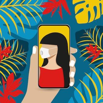 Eine junge frau, die eine medizinische maske trägt, macht ein selfie und hält das smartphone in der hand.