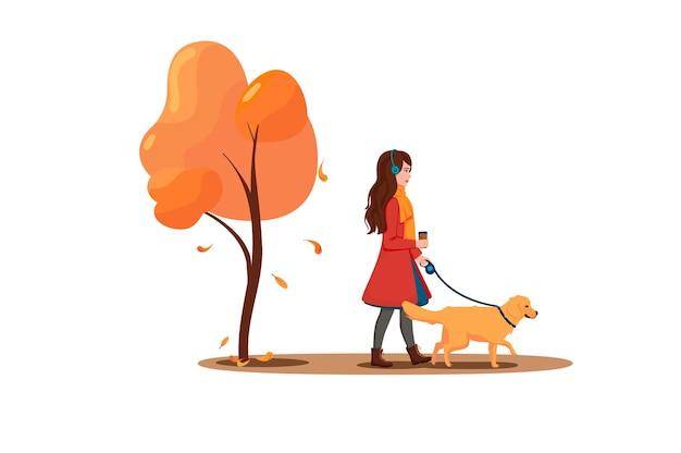 Eine junge frau geht mit einem hund im park spazieren