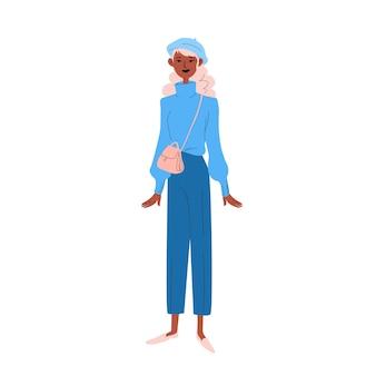 Eine junge frau in blauer kleidung mit einer baskenmütze auf dem kopf und einer kleinen handtasche über der schulter.
