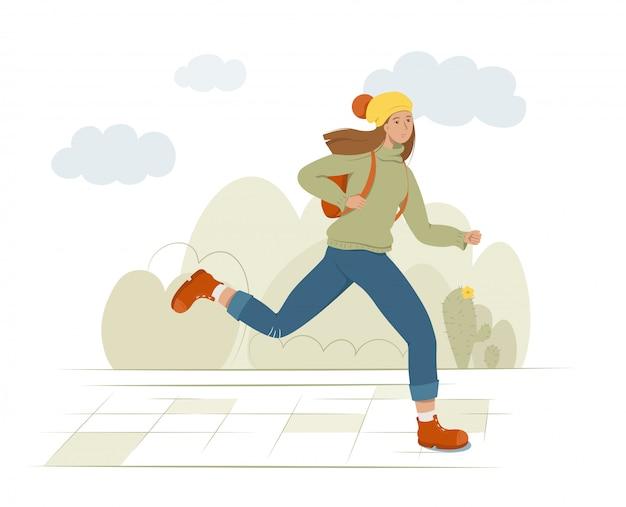 Eine junge studentin rennt mit einem rucksack auf dem rücken.