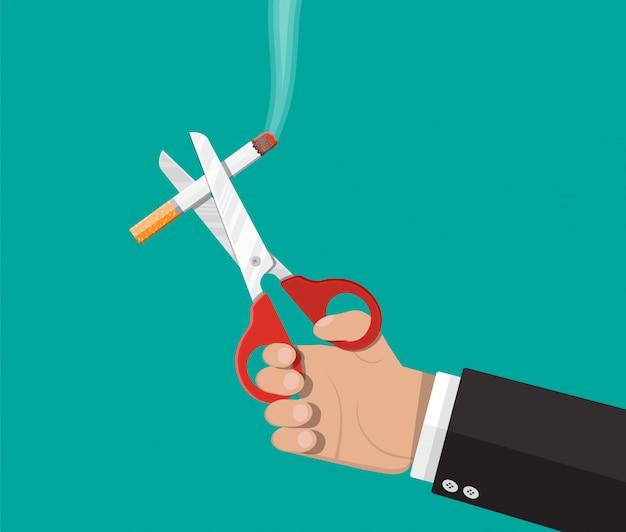 Eine schere in der hand schnitt eine zigarette.