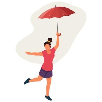 Eine sehr glückliche frau, die mitten in der regenzeit mit einem regenschirm spielt