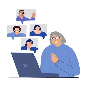 Eine süße alte frau kommuniziert mit ihren enkelkindern verwandten auf einem laptop zu hause