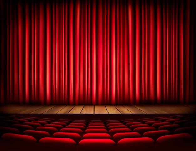 Eine theaterbühne mit rotem vorhang, sitzgelegenheiten.