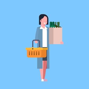 Einkaufen der jungen frau, das papiertüte und korb voll von den lebensmittelgeschäft-produkten hält