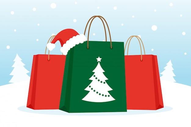 Einkaufstaschen mit weihnachtshut auf dem schnee
