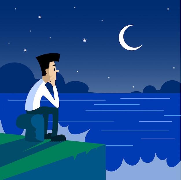 Einsamer mann, der auf dem pier nachts sitzt