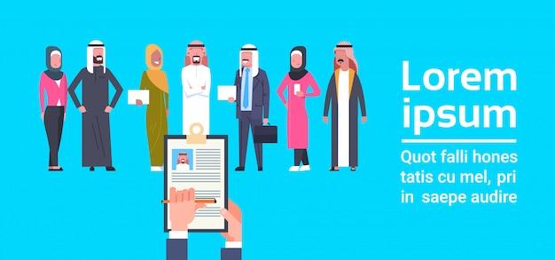 Einstellungs-hand, die die zusammenfassung wählt kandidaten von den arabischen geschäftsleuten gruppen-personalwesen-konzept-fahnenschablone hält