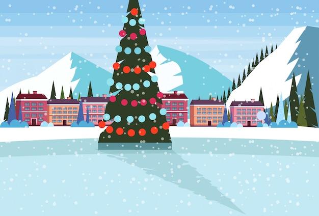 Eisbahn mit geschmücktem weihnachtsbaum im skiorthotel