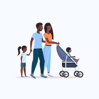 Eltern mit tochter und kleinkindsohn im kinderwagen zu fuß im freien familienelternschaft konzept in voller länge