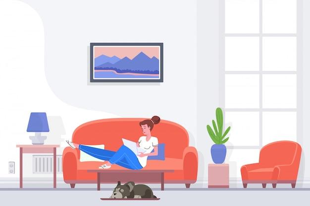 Entspannte frau, die auf couch sitzt und laptop durchstöbert, während sie zeit zu hause verbringt.