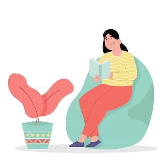 Entspannte frau, die im stuhl mit lesebuch sitzt