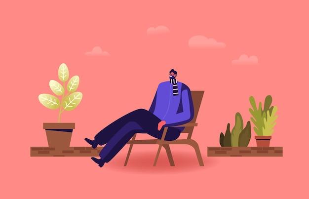 Entspannter männlicher charakter, der in einem bequemen sessel sitzt und sich auf der winterhausterrasse, dem balkon oder dem gewächshaus entspannt