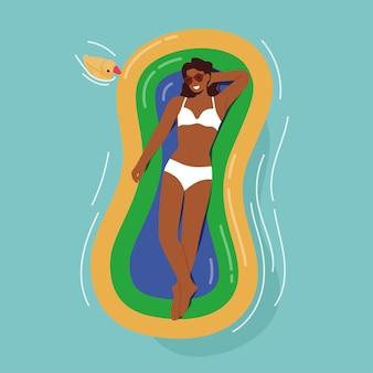 Entspannter weiblicher charakter, der den sommerurlaub genießt, auf aufblasbarer luftmatratze schwimmt, ein sonnenbad nimmt und sich bräunt