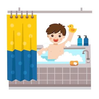 Entzückender kleiner junge, der ein bad in der badewanne mit viel seifenschaum und gummiente nimmt.