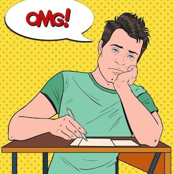 Erschöpfter männlicher student der pop-art, der während des langweiligen universitätsvortrags auf dem schreibtisch sitzt. müder hübscher mann im college. bildungskonzept.
