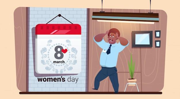 Erschrockener afroamerikaner-mann, der am 8. märz glücklichen frauen-tag des kalenders betrachtet