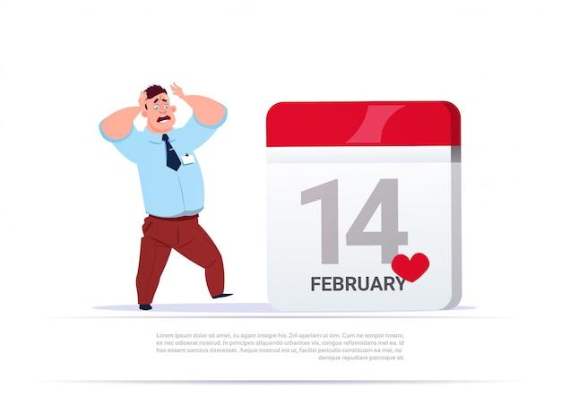 Erschrockener mann, der am 14. februar datum am kalender-valentinsgruß-tagesfeiertags-konzept betrachtet