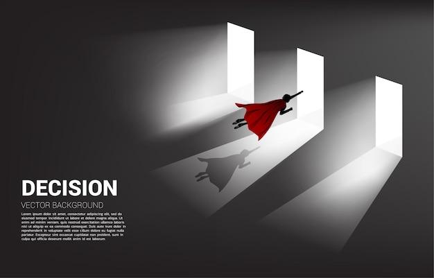 Es ist zeit, eine entscheidung in der geschäftsrichtung zu treffen. silhouette eines geschäftsmannes, der fliegt, um die tür zum betreten auszuwählen?