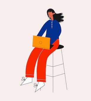 Ethnische geschäftsfrau, die mit einem laptop auf einem stuhl sitzt