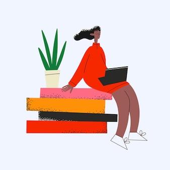 Ethnische geschäftsfrau, die mit laptop auf büchern sitzt