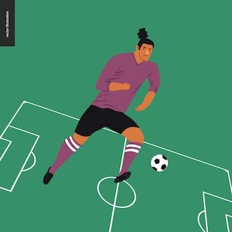Europäischer fußballfußballspieler, der einen fußball im grünen fußballplatz tritt