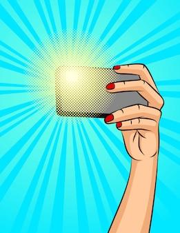 Färben sie vektorillustration einer weiblichen hand mit einem telefon. eine frau macht ein selfie