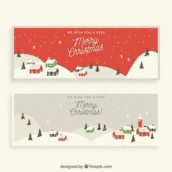 Fahnen der frohen weihnachten mit schneebedeckter stadt