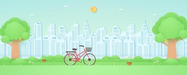 Fahrrad im garten mit baumvogel auf dem zweig schöne blumen auf grasbauhintergrund