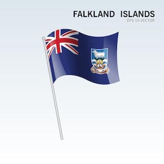 Falklandinseln, die flagge lokalisiert auf grauem hintergrund wellenartig bewegen