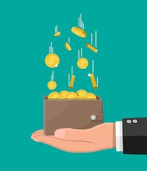 Fallende goldmünzen und lederbrieftasche in der hand
