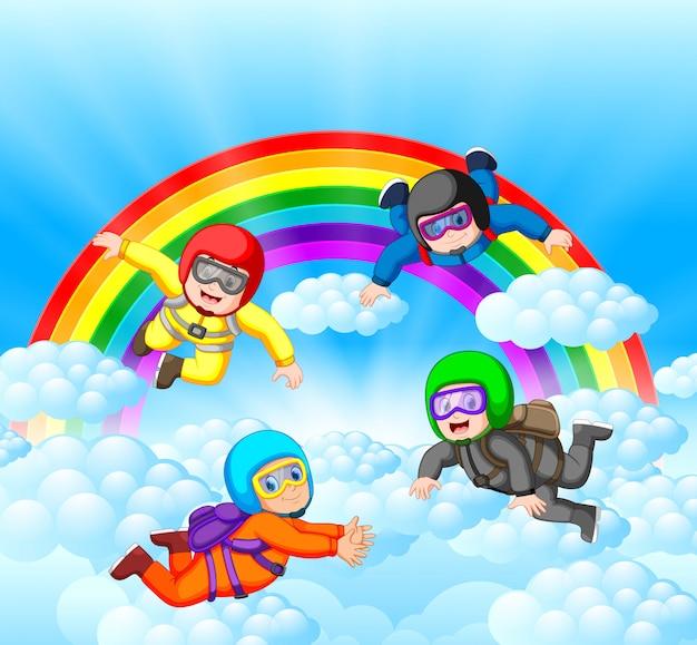 Fallschirmspringer, die spaß an der erstaunlichen wolke mit regenbogenlandschaft haben